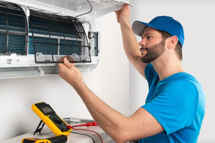 HVAC Specialist repairing a ductless heating and cooling ventilation system unit inside a client's home.