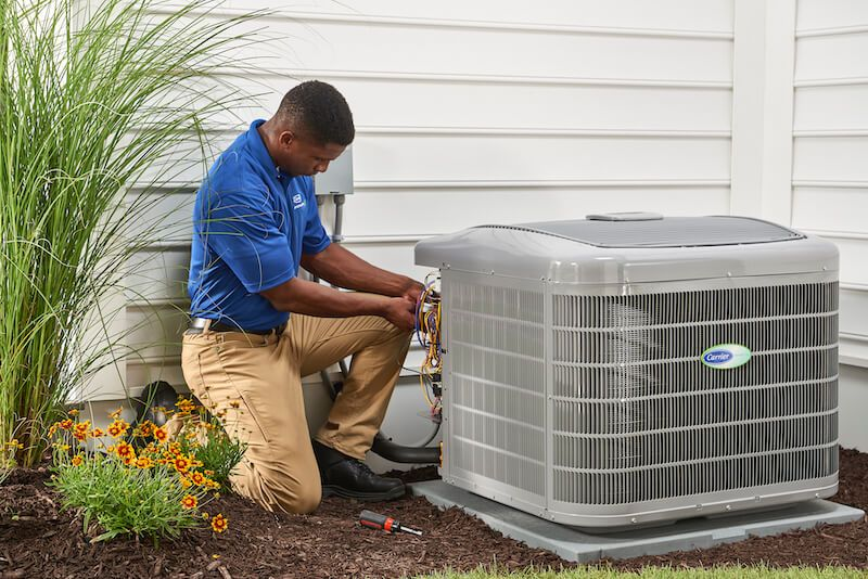 HVAC Specialist performing annual maintenance on the central air conditioner compressor