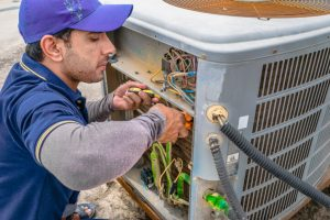 HVAC Specialist repairing the central air conditioner compressor.