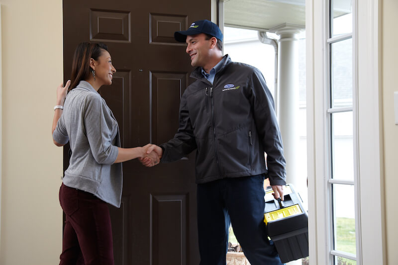 HVAC Specialist making a house call for heating repair, shaking hands with the client upon entering the home