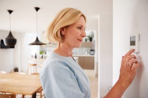 Woman adjusting her digital thermostat inside her home, kitchen and dining room in the background.
