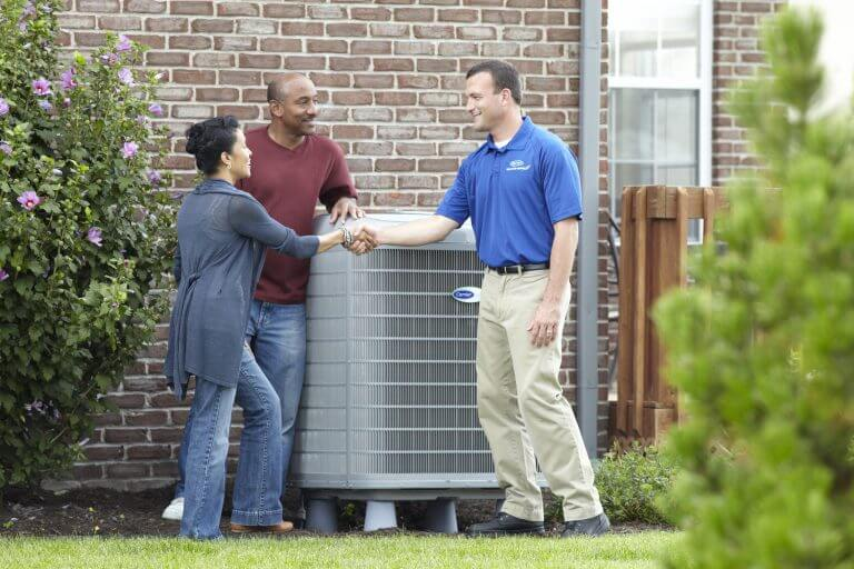 HVAC specialist consulting with a couple outside their home next to their AC system unit.