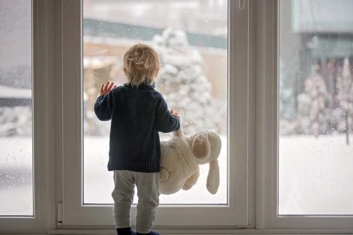A small boy with a large stuffed rabbit dangling from one hand, the other hand pressed against the patio door, watching the yard fill up with snow.