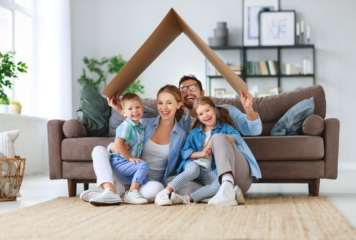 A smiling family of 4 gather together on the floor in front of the couch in their clean, bright living room, with a card-board cut-out folded into the shape of a sloped roof over their heads.