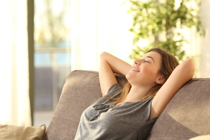A woman relaxes on her couch with her eyes closed and hands clasped behind her head.