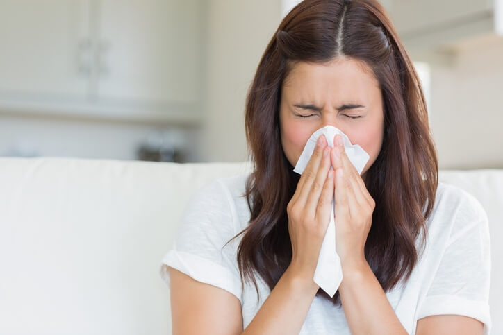 A woman with allergies blowing her nose into a tissue.