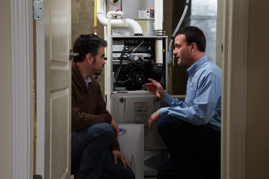 HVAC specialist consults with customer about his heating system in his home.